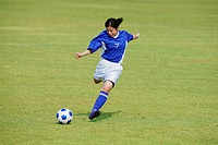 Woman In Soccer Uniform Kicking a Ball