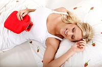 Smiling young woman lying in bed with hot_water bottle