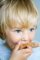 Toddler eating a bread