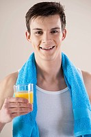young smiling man holding glas with orange juice