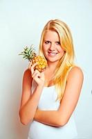 junge blonde glückliche frau mit ananas