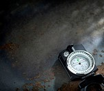 A modern black compass resting in the corner of the image on a dark blue mottled background