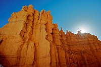 The sun just rises above a tall hoodoo.