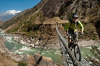 A mountain biker crosses a long steel suspension bridge in Nepal