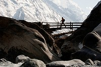 A trekker crosses a wooden bridge in the Tsum valley in Nepal