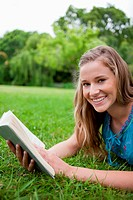 Young smiling woman lying on the grass in a park while holding a book