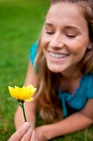 Yellow flower held by a smiling teenage girl