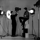 The Italian voice artist and film actor Corrado Pani poses in a photographer's studio with the American actor Joseph Walsh; Pani is sat down on a colu...