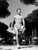 Jacques Sernas walks barefoot in a pinewood wearing a swimming trunks holding a towel. 1950.