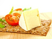 Cracker on wooden board, with soft cheese and tomato