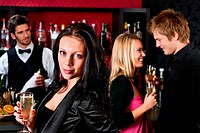 Attractive girl smiling with friends at bar