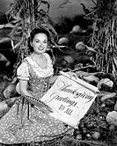 American actress and singer Ann Blyth posing with a greeting sign for the American Thanksgiving Day. USA, 1950s.