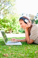 Side view of a woman with a laptop and headphones on the lawn