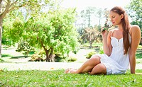 Woman sitting on the lawn while smelling a flower