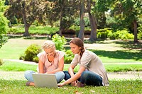 Friends sitting on the lawn with a laptop