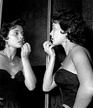 Italian actress Lucia Banti making-up in front of a mirror. 1950s.