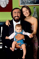 The Italian opera singer Luciano Pavarotti poses smiling for the photographer, holding his daughter Alice in his arms and with his second wife Nicolet...