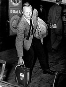 American actor Richard Widmark picking up a handbag. Rome, 1954.