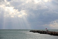 sun streaming through clouds at the south jetty at Venice Florida USA