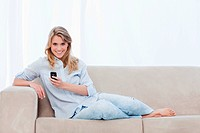 A woman sitting on a couch holding a mobile phone is smiling