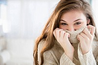Hispanic girl covering her face with sweater
