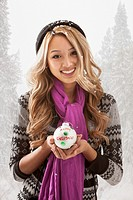 Mixed race woman holding Christmas ornament in snow