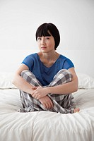 Chinese woman sitting on bed