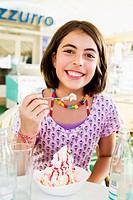 Girl eating ice cream sundae outdoors
