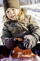 Smiling girl sledding in snow