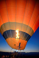 Propane heater inflating a hot air balloon at dawn with Urgup city lights Cappadocia Turkey