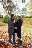 Smiling couple standing in autumn leaves