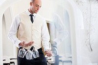 Waiter carrying wine glasses in restaurant