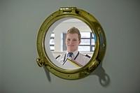 Student looking through ships porthole