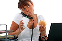 young woman eating hamburger and drinking out of a straw while making a call