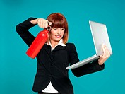 attractive businesswoman, using fire extinguisher on laptop