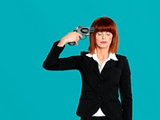 young businesswoman, pointing gun to her head