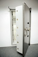 opened solid old bank vault door with combination lock