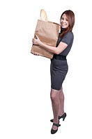 A beautiful woman grocery shopping holding a brown paper bag