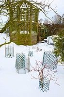SNOW COVERED GARDEN WITH GAZEBO AND WIRE NETTING PROTECTING OVERWINTERING SHRUBS
