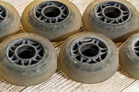 old worn out wheels for inline skating on wooden surface