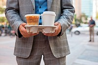 Businessman holding takeaway coffee cups