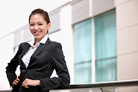 Businesswoman smiling and leaning on metal railing
