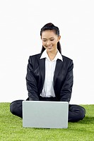 Young Asian businesswoman sitting cross-legged on grass using her laptop