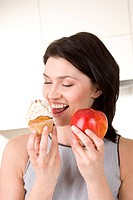 Woman with cupcake &amp; apple in hand