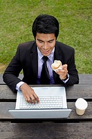Young Asian businessman having a light snack in a park with his laptop