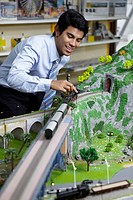 Young Asian businessman playing with a train set