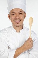 Asian chef holding wooden spoon