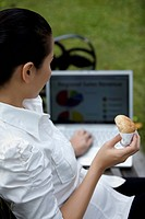 Mid adult businesswoman working while eating