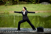 Mid adult businesswoman in yoga pose at the park