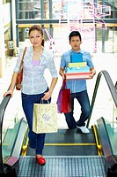 Woman walking while man carry shopping items